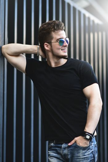 Young stylish and confident happy handsome guy model in t-shirt lifestyle in the street in sunglasses