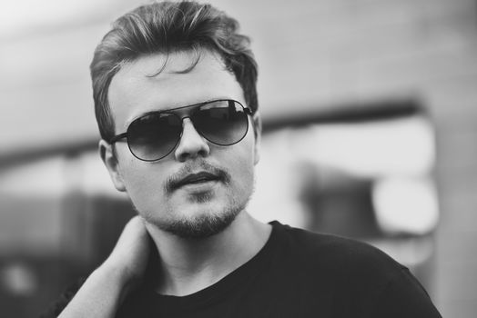 Handsome stylish man with sunglasses and modern hairstyle and beard. Outdoor in the street. black and white photo