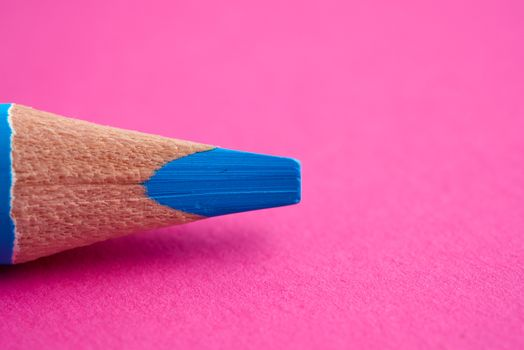 sharpened blue pencil on a pink background