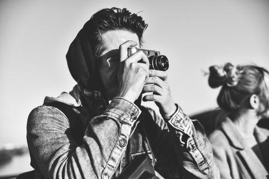 Stylish man photographing on retro camera. Tourist stay on the bridge and make a photo.