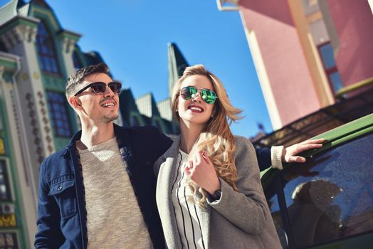 Couple in sunglasses standing near the car and looking for new apartment