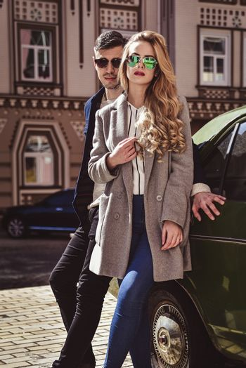 Fashionable couple in sunglasses stand at street near the car