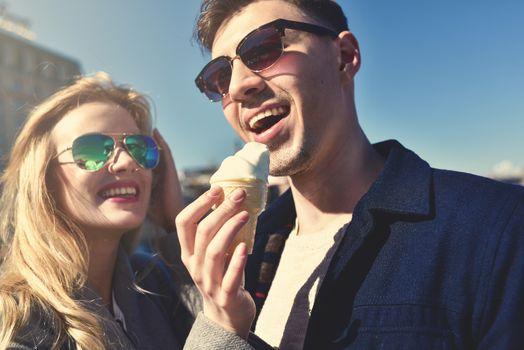 Happy romantic caucasian couple in sunglasses. Funny girl eat the ice cream