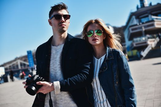 Romantic couple walk at the street with photo camera