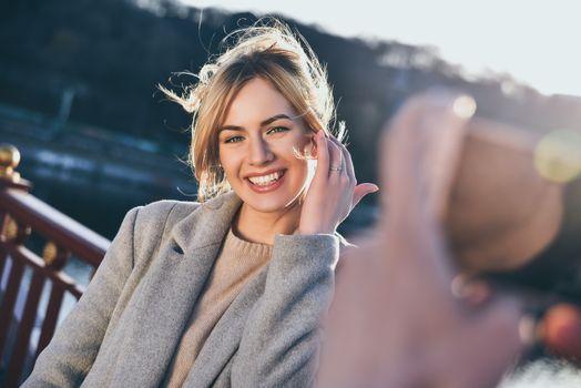 Cheerful girl look at the camera in beautiful sunny day. Enjoying a sunny mood