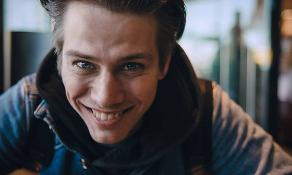 Close up photo of handsome Caucasian man looking and smiling at camera with happy cheerful expression.
