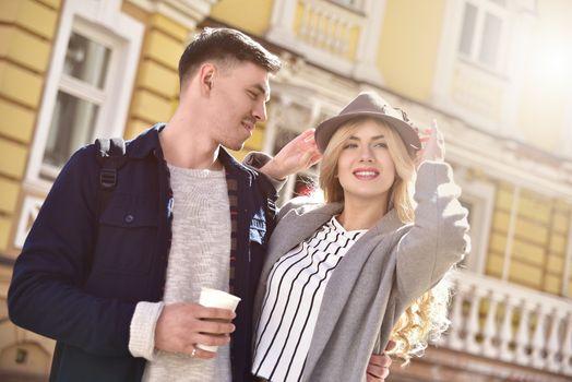 Stylish couple walking at the street having fun