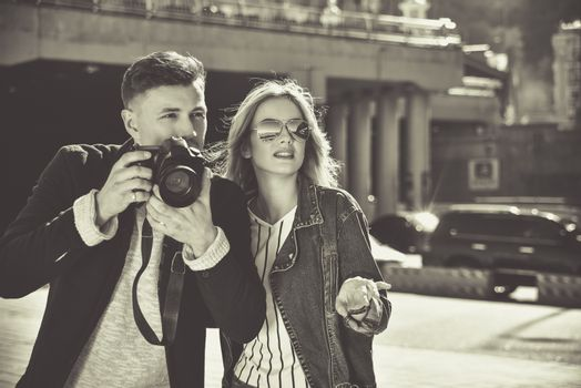 Romantic couple walk at the street with photo camera in BW