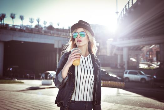 Beautiful girl with juice in sunglass walking at the street on urban style