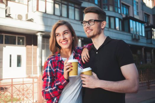 Awesome couple walking at street and drink a coffee