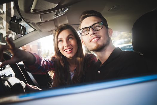 Enjoying travel. Beautiful young couple sitting on the front passenger seats and smiling while handsome man driving a car.