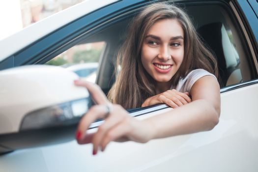 Portrait of cute smiling girl sit in the car and look at the car mirror
