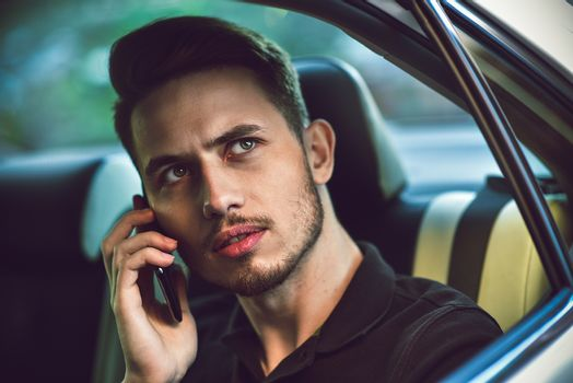 Handsome man sit in the back seat of the car and use a phone.
