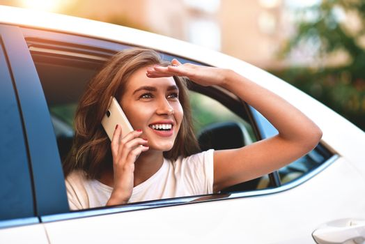 Beautiful woman with phone smiling while sitting on the back seat in the car.
