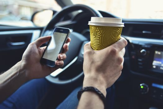 Man arms hold a coffee and phone in automobile