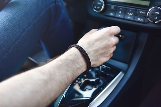 Hand Holding Automatic Transmission In his Car