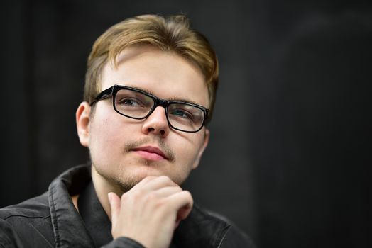 Serious young caucasian man wearing black glasses looking up and thinking