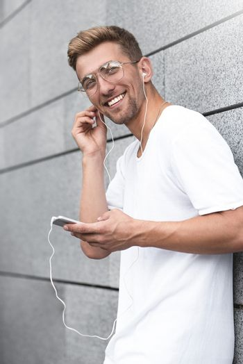 Earphones concept. People, technology, travel and tourism - man with earphones, smartphone on city street and listening to music over gray wall background