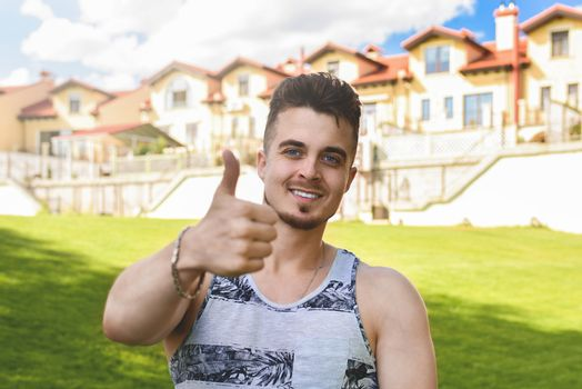 Attractive resting man with thumb up. beautiful cottages in the background