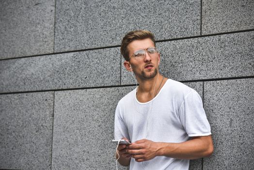 People, technology, travel and tourism - man with earphones, smartphone on city street and listening to music over gray wall background