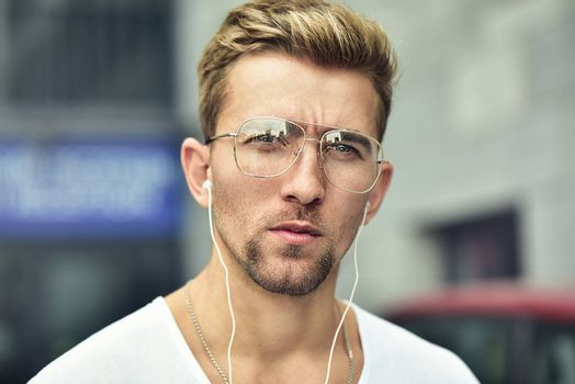 People, technology, travel and tourism - man with earphones on city street and listening to music.