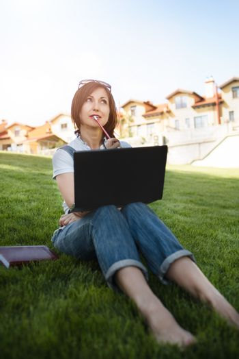 Portrait of pretty adult woman sitting on green grass in park with laptop on legs, spending summer day working outdoor, using laptop and wireless Internet for online work. Lifestyle