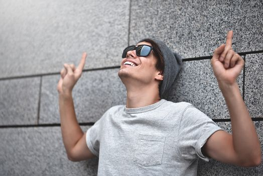 Cheerful guy dressed in gray t-shirt, sunglasses and hat at the street, show a big sale, or nice offer. Advertise concept. People, travel and tourism - man with Sunglasses on city street and guy show with his finger something over gray wall background