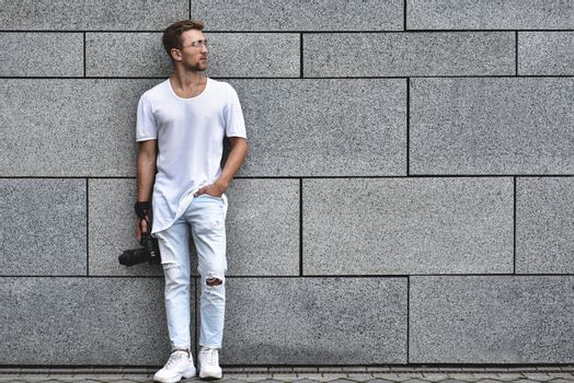 Picture of handsome Caucasian guy on grey textured wall in white T-shirt and white jeans with camera hanging on strap on his arm.