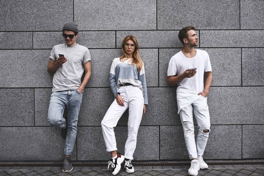 Fashion portrait of Three best friends posing at street, wearing stylish outfit and jeans against gray wall .