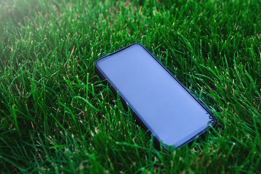 Smartphone and black screen on grass background