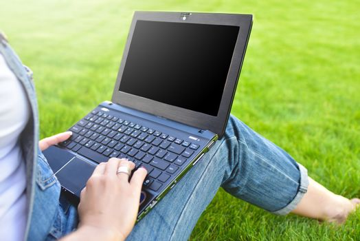 Close view of woman sitting on green grass in park with laptop on legs, spending summer day working outdoor, using laptop and wireless Internet for online work.