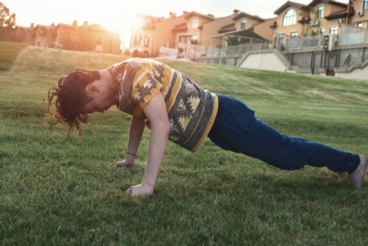 Sport. Athlete doing push-ups at sunset in the park . skinny guy exercising and trying to get fit.