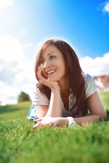 summer-vacation, adult woman relaxed lying on green grass in an outdoor park. girl in sunglasses enjoying nature lying on grass