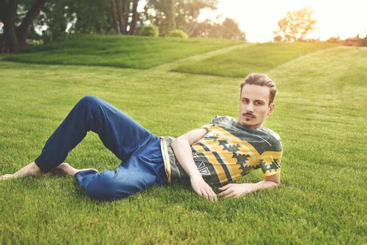 handsome man on the grass resting in park