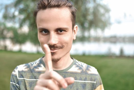 a guy with a sly expression on his face, shows a finger gesture, do not try to deceive me