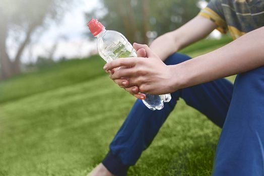 Young caucasian man runner relaxing holding drinking water bottle and sitting on grass in the park outdoors after sport at early morning time, Exercise and healthy concept. summer time