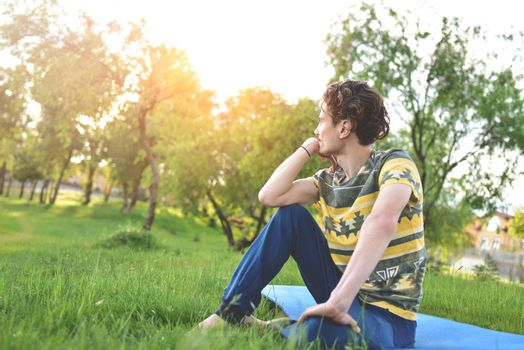 handsome stylish guy enjoys nature and dreams about something sitting in the park. peaceful sight. summer mood