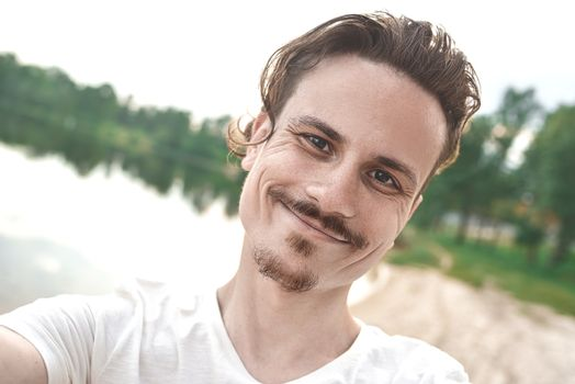 Handsome caucasian guy takes a selfie at the beach - people, lifestyle