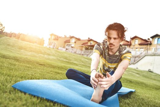 Man performing yoga young fitness man outdoor doing exercise