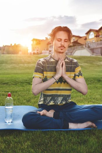 Young man meditating outdoors in the park, sitting with eyes closed and his hands together