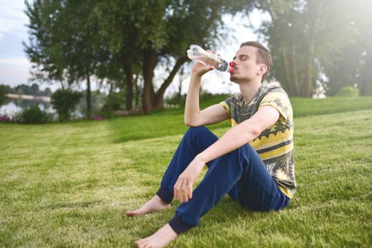Young man sitting on the garden and drinking water after running