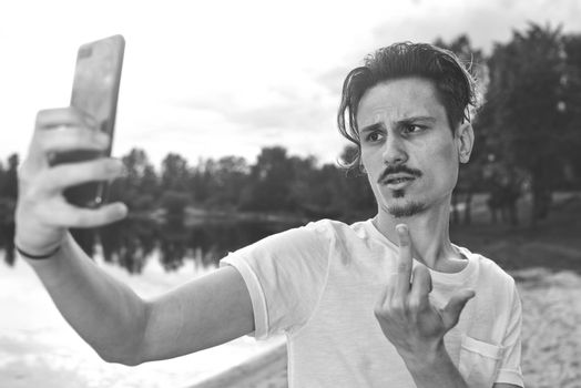 Portrait of angry confused aggressive in bad mood guy irritably speaks on the phone on the background of the lake