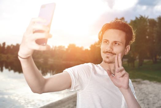 portrait of Young handsome stylish smiling guy makes selfie against the lake. beautiful nature