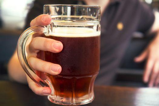 Dark beer in mans hand,mug of beer,