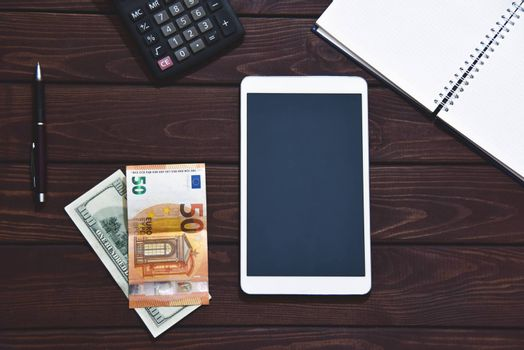 Top view of tablet, smartphone, calculator, notepad on white background, planning personal income, financial concept. Hand is typing on the calculator for money plan.