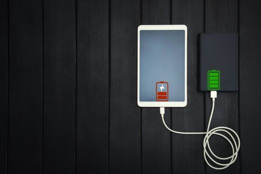 power bank loads tablet PC, smartphone - isolated on wooden background. charging concept. free copyspace