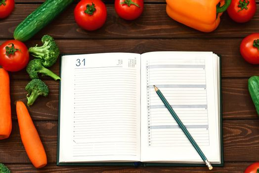Diet regimen, vegetable image and diet menu plan on Notepad. The guy is recording a dietary program. new cooking recipes
