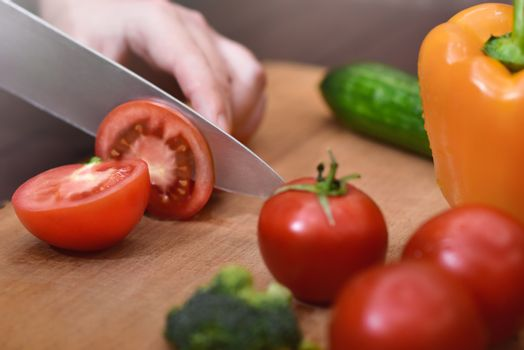 Man slicing a tomato , Bell peppers, and cucumbers with a chef's knife. Organic ingredients for healthy eating