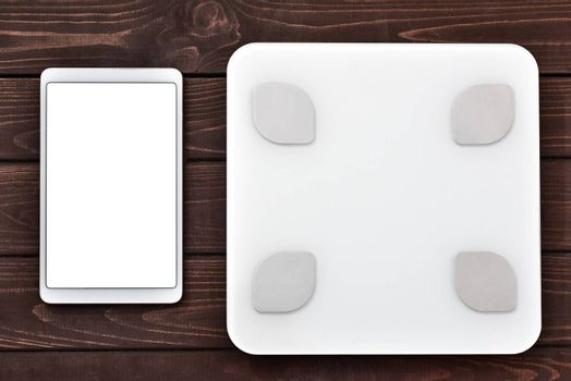 Glycemic index Fitness and weight loss concept, white scale and tablet on wooden table, top view,