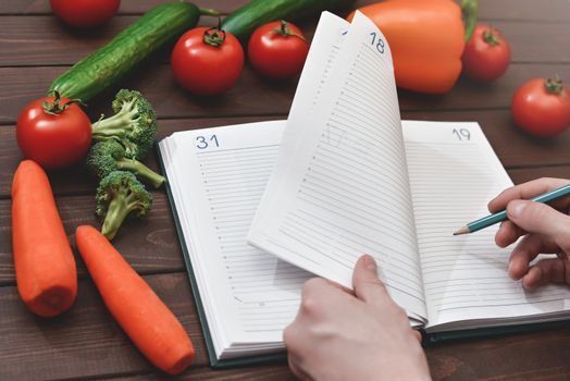 Dieting concept with a smartphone and a notepad and pen surrounded by lots of healthy vegetables.